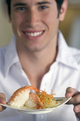 Young man with plate of Japanese food, smiling, portrait (differential focus)