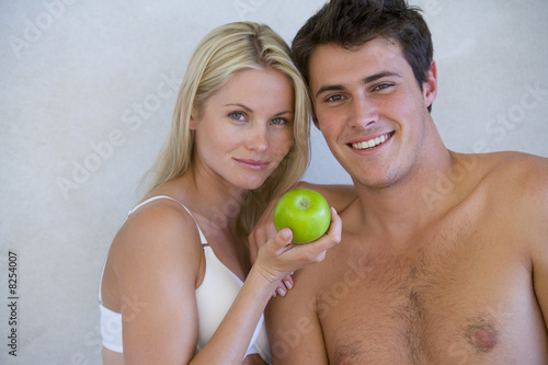 Young couple, woman in underwear with apple by bare chested man, smiling, portrait