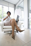 Businesswoman with laptop computer in armchair, portrait, low angle view