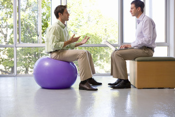 Businessman on exercise ball in meeting with colleague using laptop computer in exercise studio, side view
