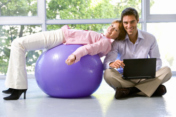 Businessman with laptop computer on floor in exercise studio by colleague on exercise ball, smiling, portrait