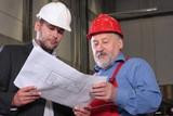 supervisor and older worker over blueprints poster