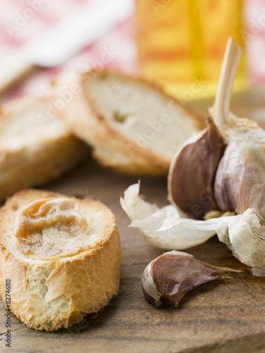 Cloves of Roasted Garlic spread on Toasted baguette