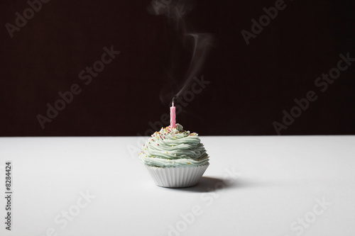 Single cupcake with blown out birthday candle