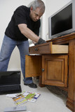 Burglar looking through drawers in house