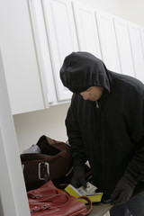 Burglar stealing money from house, close-up