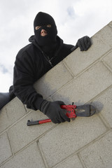 Masked thief climbing wall
