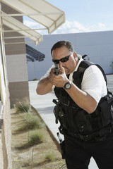 Security guard aiming with gun outdoors