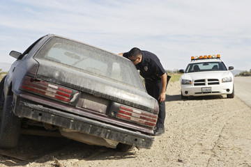 Police officer looking into abandoned car on roadside