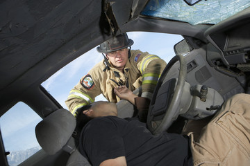 Firefighter looking into crashed car, view from interior