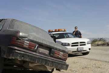 Police officer talking on CB radio on roadside