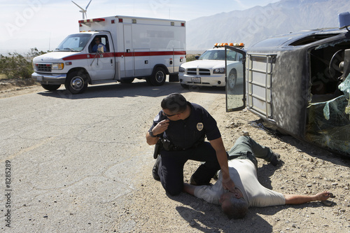 Policeman checking pulse of car crash victim