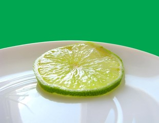 piece of green lime on a white plate.Green backgrownd