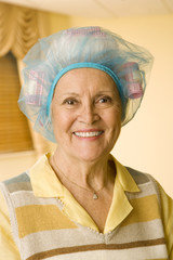 An elderly woman wearing curlers
