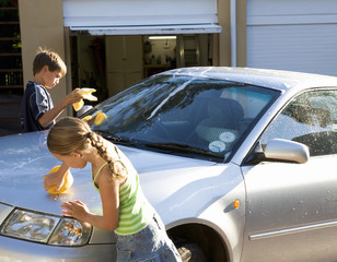 Young girl and boy washing a car