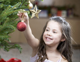 A young girl putting a decoration on a Christmas tree