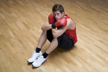A young man wearing boxing gloves