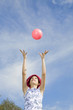 Girl throwing pink ball in air