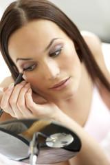 Young woman applying eye liner