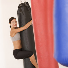 A young woman hugging a punch bag