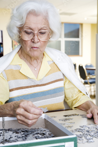 An elderly woman completing a jigsaw