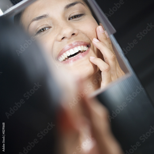 A young woman looking in a mirror