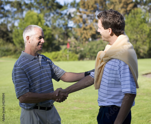 Two men shaking hands on a golf course