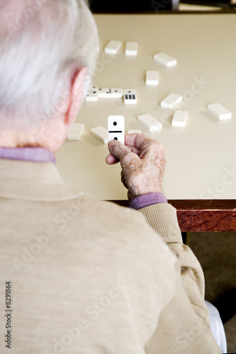 An elderly man playing dominoes