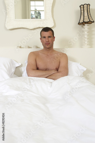 Young man sitting up in bed, arms folded