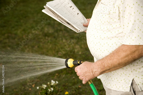 A senior man watering the garden