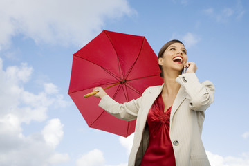 A businesswoman standing underneath an umbrella holding a mobile phone