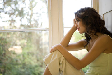 A young woman sitting in a window