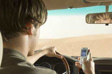 A young man using a mobile phone whilst driving