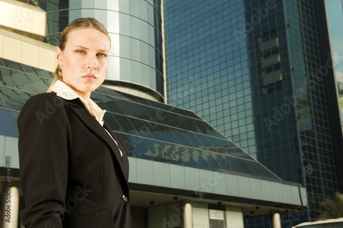 A businesswoman standing in front of a modern building