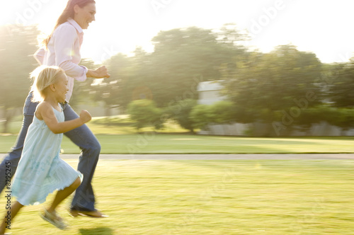A mother and her young daughter running in a park