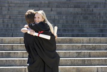 Two graduates embracing