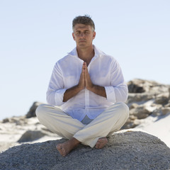 A man sitting on rocks performing yoga