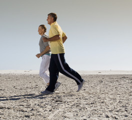 A mature couple jogging on a beach