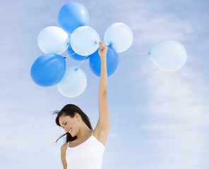 A woman holding a bunch of balloons