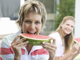 Two women eating watermelon