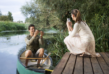 Young woman taking a photo of her partner's fishing success