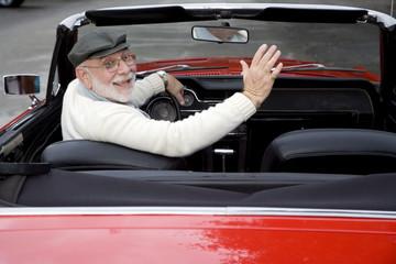 A senior man driving a sports car