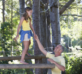 A father helping his daughter balance on a climbing frame