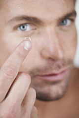A young man inserting a contact lens