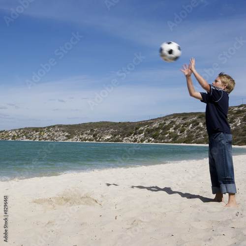 A young boy playing with a football on a beach