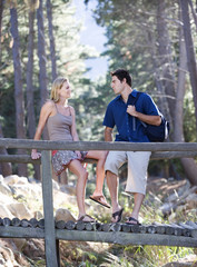 A young couple standing on a wooden bridge