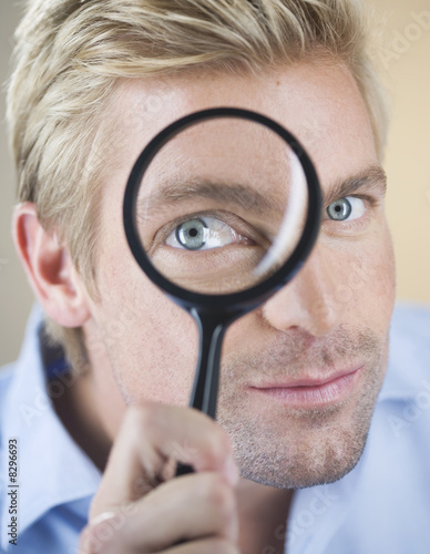 A young man looking through a magnifying glass