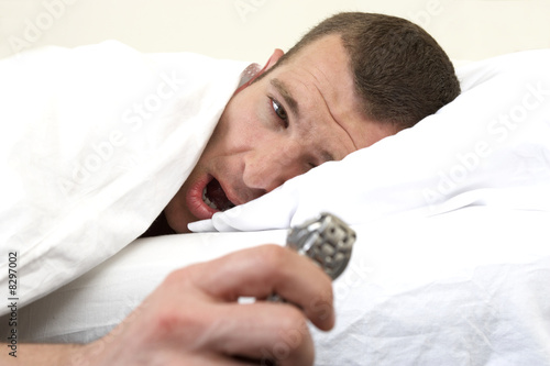 Young man laying in bed, looking at watch