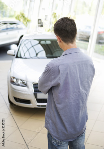 A young man looking at a new car