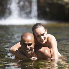 Young couple embracing in a natural pool